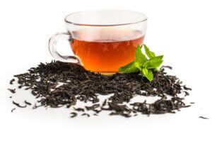 Tea Leaves surrounding a glass of black tea