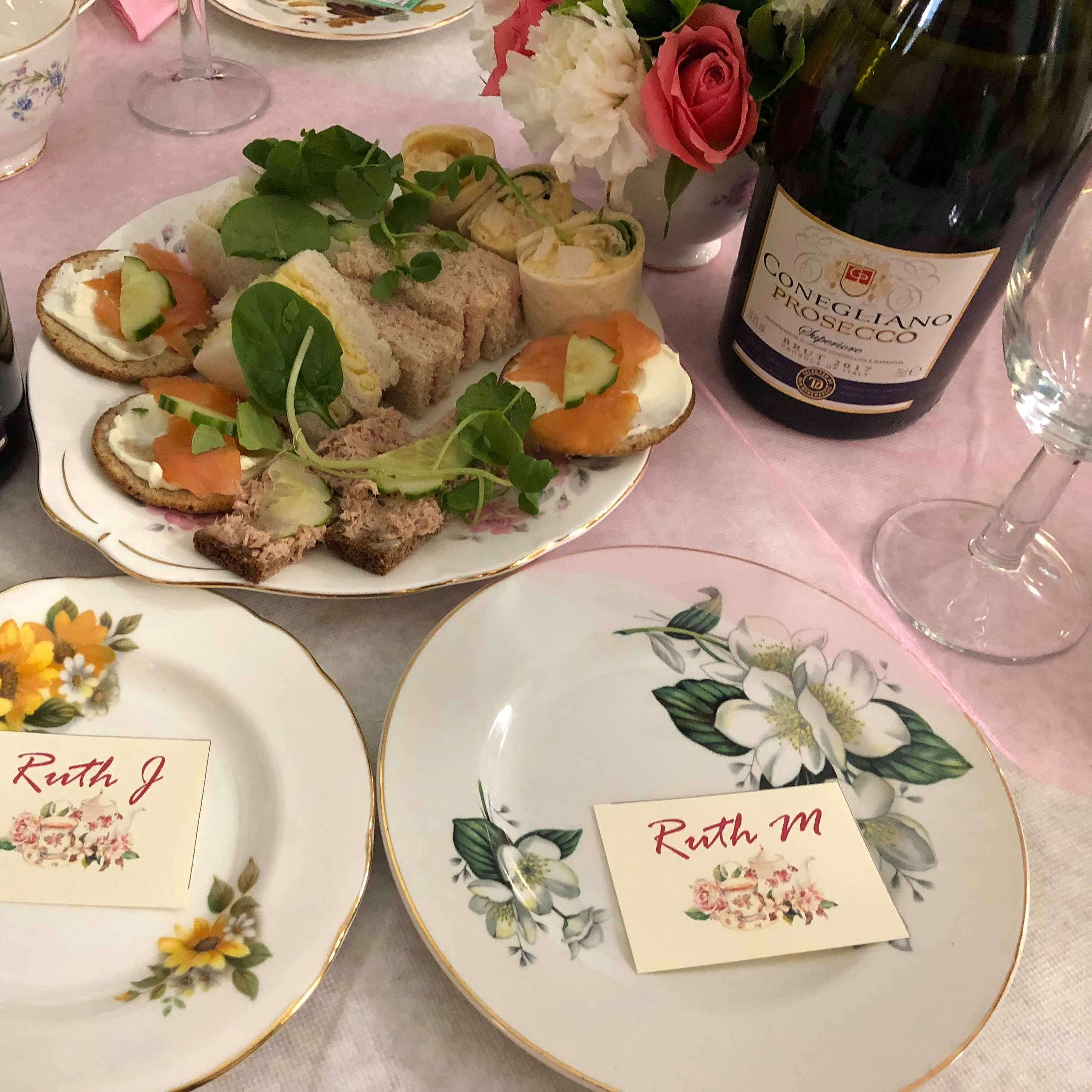 Photo shows a plate of sandwiches, flowers, and Prosecco at an Afternoon Tea Party