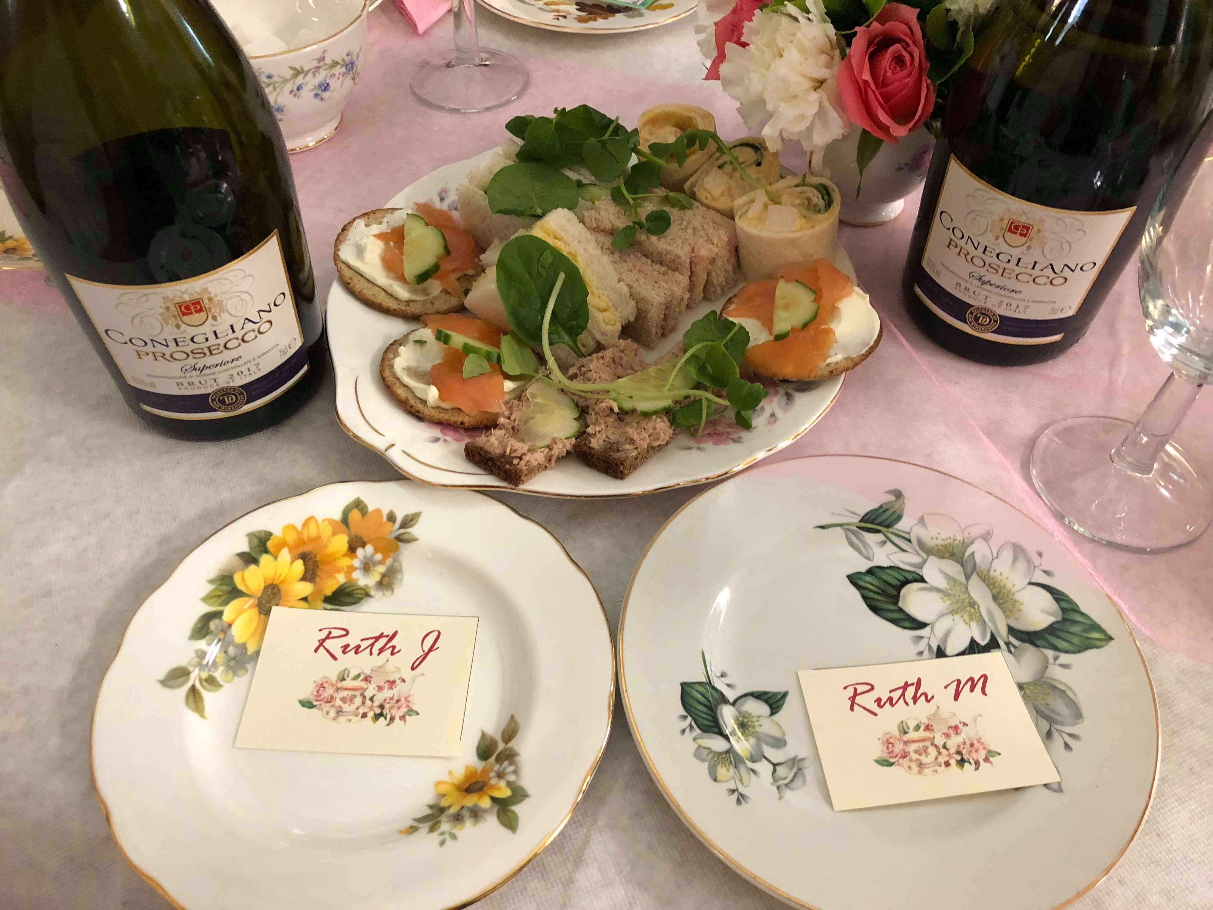 Photo shows dainty sandwiches and bottles of Prosecco amongst vintage china at a Tea Party